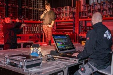 Einer der Drehorte für das neue Simultan-Video: die Lagerhalle der Veranstaltungstechnikfirma LSG Action Lighting. Im Bild Kameramann David Rötzschke (links) beim Videodreh mit Sebastian Fischer von Simultan und André Luderer, Inhaber von LSG.