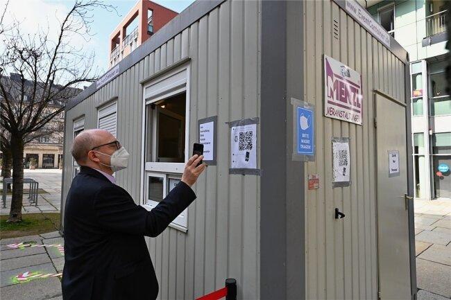 Oberbürgermeister Sven Schulze registriert sich mithilfe eines QR-Codes für den Schnelltest. Die Station auf dem Jakobikirchplatz ist eine von vier, die nun in Betrieb gehen sollen.