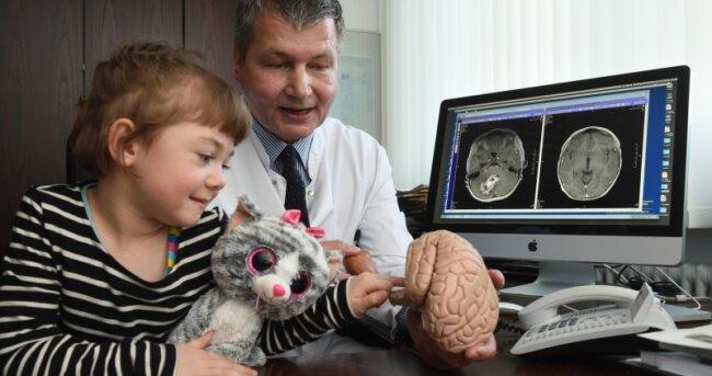Jamina Freitag (ohne ihre Katze wollte sie nicht aufs Foto) lässt sich von Prof. Ralf Steinmeier, Chefarzt der Klinik für Neurochirurgie, erklären, wo der Tumor in ihrem Kopf saß. Auf dem linken Bildschirm-Bild ist er zu sehen.