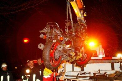 """<p class=""""artikelinhalt"""">Fassungslos beobachten Rettungskräfte, wie die stark beschädigte Maschine des tödlich verunglückten Motorradfahrers abtransportiert wird. Die Bundesstraße 173 war am Donnerstagabend nach dem Unfall am Ortseingang von Oederan für mehrere Stunden gesperrt.</p>"""