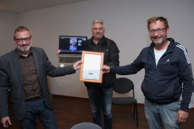 Alexander Ziron (rechts) nimmt von Manfred Deckert, Präsident des VSC Klingenthal, Heiko Krause (im Video), Präsident des Sächsischen Skiverbandes, und Andreas Kunoth (links), VSC-Vizepräsident, Glückwünsche zur Auszeichnung mit der Ehrennadel des Deutschen Skiverbandes in Silber entgegen.