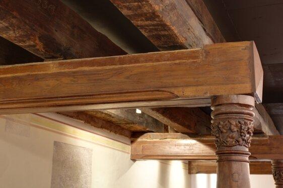 Mächtige alte Deckenbalken und neugotische Rundsäulen.