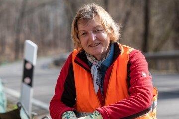 Angela Schubert befestigt am Krötenzaun eine Plane.