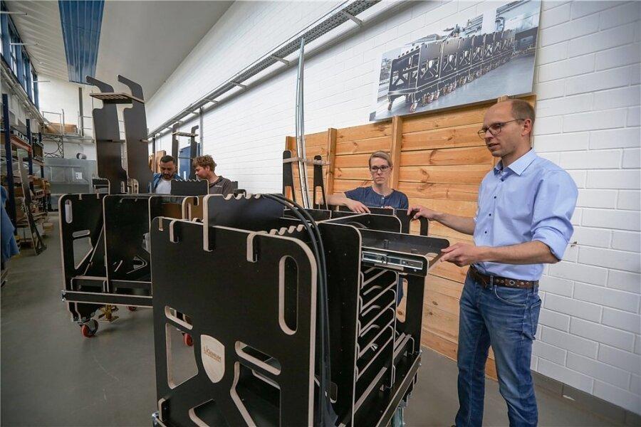 """Aus der TU Chemnitz heraus gegründet: Das Unternehmen """"LiGenium"""" stellt unter anderem Materialwagen aus Holz für die Autoindustrie her. Im Bild vorne Christoph Alt (rechts) und Angela Grimmer."""