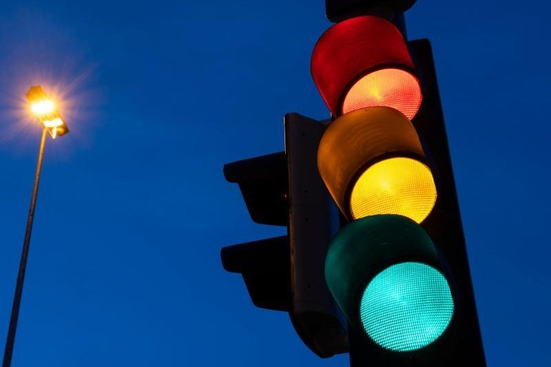 Eine Ampel zeigt am frühen Morgen die Farben rot, gelb und grün.