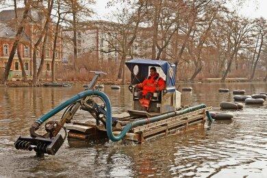 """Der Schwimmbagger, der den Schlamm vom Boden des Langen Teiches in Zwickau holt, ist wieder im Einsatz. Wie das Garten- und Friedhofsamt der Stadt auf Anfrage sagte, werden die mit dem Beginn der Frostperiode unterbrochenen Arbeiten fortgesetzt. Bisher wurden mehr als 1000 Tonnen Schlamm in den sogenannten Geo-Tubes an der Melzerwiese getrocknet und anschließend entsorgt. """"Die Schlammmasse entspricht der Kalkulation"""", sagte Rathaussprecher Mathias Merz. Mehrkosten seien nicht zu erwarten. Ab der kommenden Woche soll der Teich abgefischt und dieFische in den Schwanenteich umgesetzt werden. Danach wird mit dem Ablassen des Wassers begonnen. Nach Ostern sollen die Arbeiten mit dem zweiten Bauabschnitt fortgesetzt werden. Dabei soll unter anderem der Boden modelliert, das Ufer gestaltet und die Terrasse saniert werden.nkd"""
