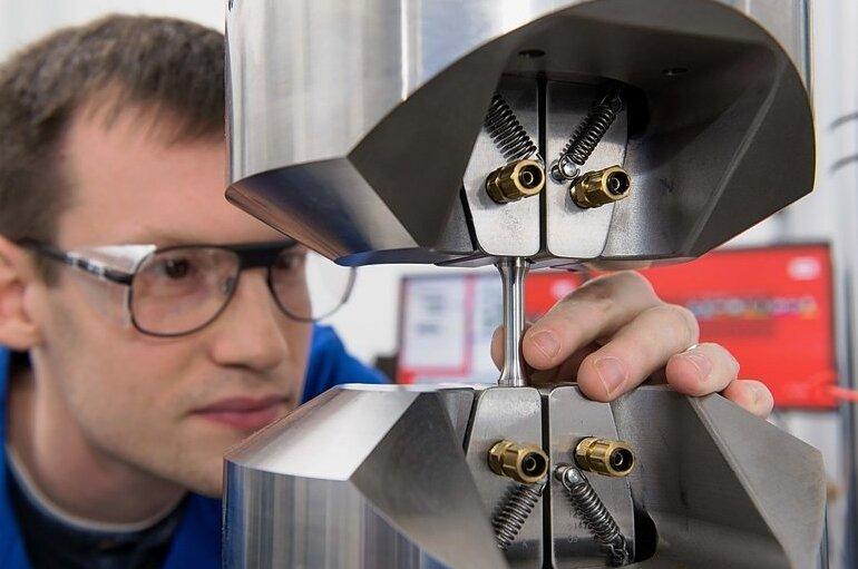 Ralf Eckner, wissenschaftlicher Mitarbeiter am Institut für Werkstofftechnik, testet den neuen Werkstoff auf Zugfestigkeit.