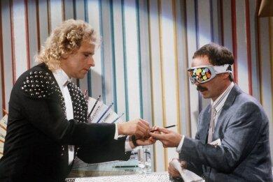 """Denkwürdige Sendung: Moderator Thomas Gottschalk (links) reicht seinem Wettkandidaten, dem damaligen Chefredakteur des Satiremagazins """"Titanic"""", Bernd Fritz, während der ZDF-Show """"Wetten dass ...?"""" einen Buntstift. Dieser enthüllt nach seiner Wette, bei der er die Farbe von Buntstiften am Geschmack erkannt haben will, dass er unter der Brille durchgeguckt habe."""