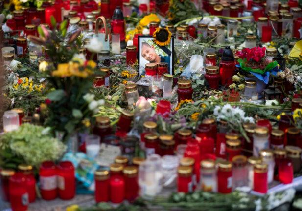 Ein Foto des Opfers steht am Tatort zwischen zahlreichen Blumen und Kerzen. Nach einem Streit war in der Nacht zu Sonntag in der Innenstadt von Chemnitz ein 35-jähriger Mann erstochen worden. Die Tat war Anlass für spontane Demonstrationen, bei denen es auch zu Jagdszenen und Gewaltausbrüchen kam.