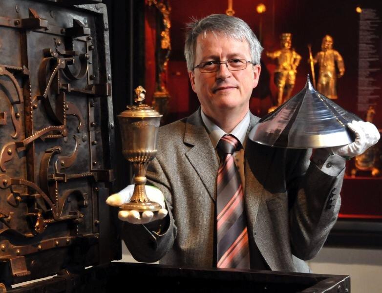 """<p class=""""artikelinhalt"""">Museumsleiter Ulrich Thiel zeigt einen Silberpokal für den Stadtkommandanten von Seydewitz von 1830 und eine Siliciumspitze und schlägt damit den Bogen von der Vergangenheit zur Gegenwart.</p>"""
