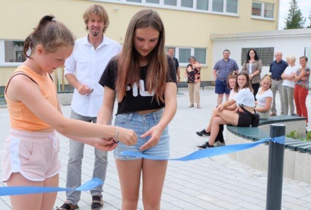 Die elfjährige Felice aus der Klasse 5b (links) und ihre zwölfjährige Klassenkameradin Luna durften das Band zur Eröffnung des sanierten Bereiches zwischen Turnhalle und Schule zerschneiden.