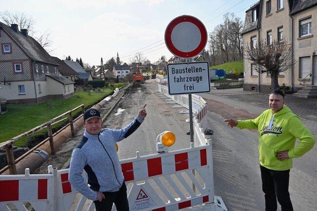 Anwohner Manfred Klein (links) und Frank Ulbricht stehen an der Baustelle der Mittweidaer Straße in Ottendorf in Richtung Krumbach.