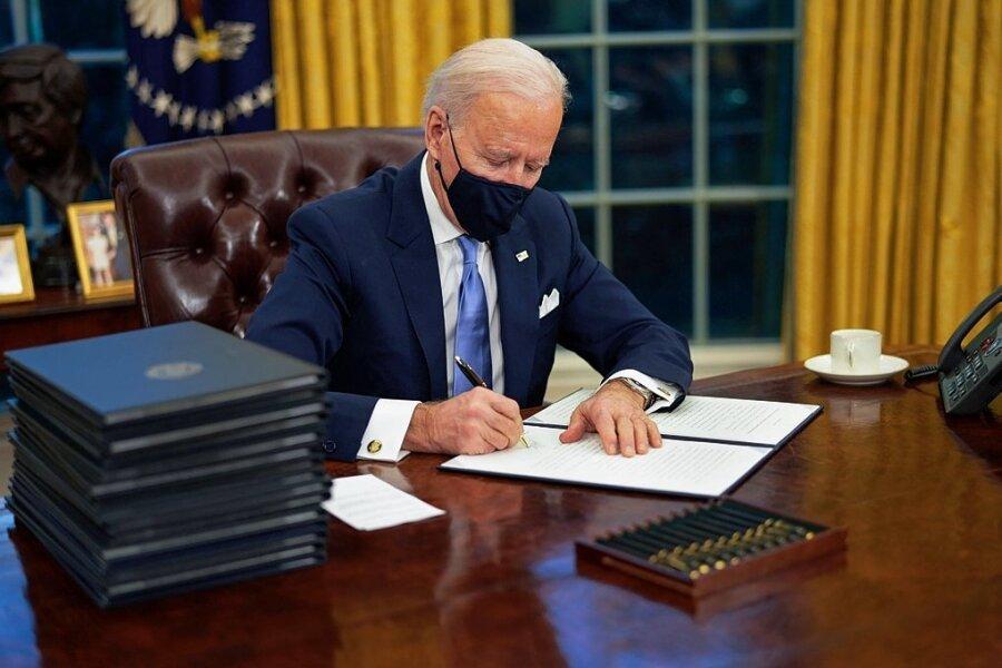 US-Präsident Joe Biden unterzeichnet im Oval Office seine ersten Dekrete. Mit einem regelrechten Feuerwerk an Verordnungen schon am ersten Arbeitstag will er demonstrativ eine Wende in der US-Politik einleiten.
