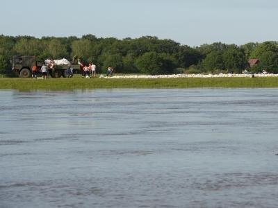 Freiwillige Helfer und Bundeswehrsoldaten stapeln Sandsäcke am Deich in Dömitz an der Elbe.