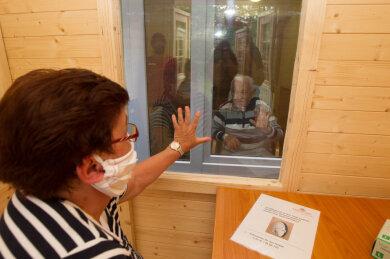 Karin Gottschald besucht ihren 100-jährigen Vater in der KS Seniorenresidenz. Sie ist froh, ihn wieder sehen zu können. Die Angehörigen sitzen für Besuche derzeit in einer Holzlaube vor dem Heim, die Bewohner in einem Zimmer des Gebäudes. Fenster sind dazwischen. Sprechen kann man miteinander nur über ein Babyfon.