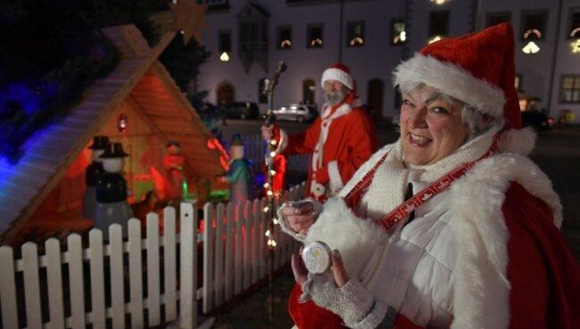 Weihnachtsfrau Solveyg Friebel und Weihnachtsmann Matthias Gottschalk beschenken in der Freiberger Innenstadt Kinder.