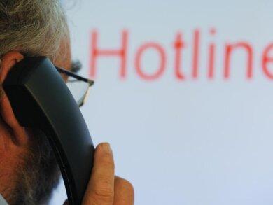 Ein Mann hält einen Telefonhörer vor dem Schriftzug «Hotline» auf einem Computermonitor.