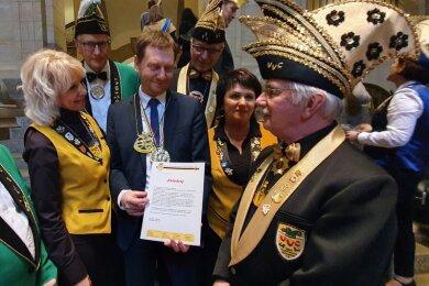 Bei der Übergabe der Einladung zum Plauener Karnevalsumzug am 23. Februar (von links): Ute Hüller vom VVC, Ministerpräsident Michael Kretschmer (CDU), Ingrid Reinhold vom VVC und Joachim Kriester, VVC-Präsident.,