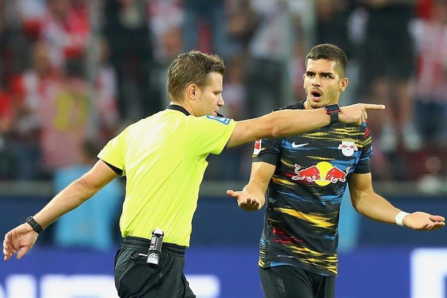 Schiedsrichter Felix Brych zeigt nach Videobeweis auf Tor für Köln, RB-Stürmer André Silva kann es nicht fassen.