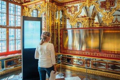 Eine Besucherin schaut in die ausgeraubte und nun leer ausgestellte Vitrine im Juwelenzimmer des Historischen Grünen Gewölbes. Doch was passiert in der Ausstellung, falls die gestohlenen Stücke nicht wieder auftauchen? Diese Frage beschäftigt das Museum.