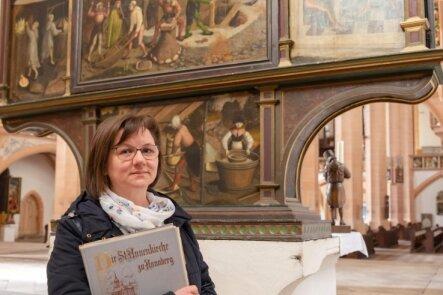 Anja Schnering, die Leiterin des Führungsdienstes der evangelisch-lutherischen Kirchgemeinde Annaberg-Buchholz, vor der berühmten Rückseite des Bergaltars. Er wurde im Mai 1521 in der St. Annenkirche eingeweiht.