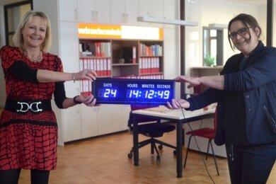 Heike Teubner (links) und Nicole Leistner präsentieren die neue Countdown-Uhr in der Beratungsstelle Auerbach: Am Freitag blieben noch 24 Tage für die Anmeldung im Klageregister.