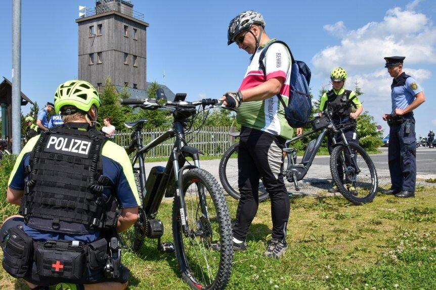 Hannes Festag von der Fahrradstaffel der Polizeidirektion Leipzig sieht sich auf dem Plateau des Fichtelbergs das E-Bike eines Radfahrers aus Franken genauer an. Die Verkehrssicherheit der Pedelecs stand bei der Kontrolle im Vordergrund. Umbauten und Tuning der unerlaubten Art wurden diesmal nicht festgestellt.