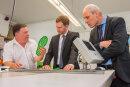 Firmenchef Hartmut Funke (links) erklärt Ministerpräsident Michael Kretschmer und Eibenstocks Bürgermeister Uwe Staab  die Funktionsweise der innovativen Sohle.