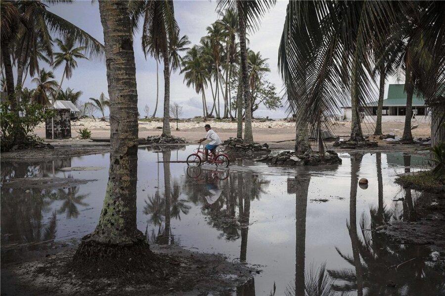 Nach dem Sturm ist vor dem Sturm: Ein Junge radelt über ein geflutetes Gelände eines Atolls, das zu Tuvalu in der Südsee gehört. Das Wasser holt sich immer mehr Land. Manche der alten Kokospalmen könnten beim nächsten Unwetter ein Opfer des Meeres werden.