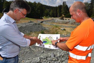 Hinterm neuen Parkplatz entsteht neues Grün: Auf dem Plan von Bürgermeister Olaf Schlott (links) und Bauhof-Chef Andreas Porkert ist das gut zu sehen.