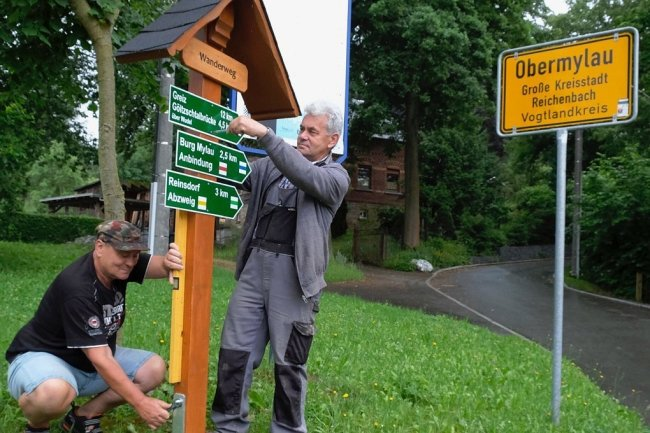 Ulrich Sörgel (stehend) und Michael Reumann beim Aufstellen des nagelneuen Wanderwegweisers an der Ecke Hauptstraße/Friesener Weg im Reichenbacher Ortsteil Friesen.