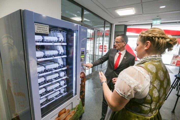 Michael Kreuzkamp, Vorstandsvorsitzender der Sparkasse, und Sarah Kretzschmar vom Biohof Kretzschmar am Eier-Automaten.