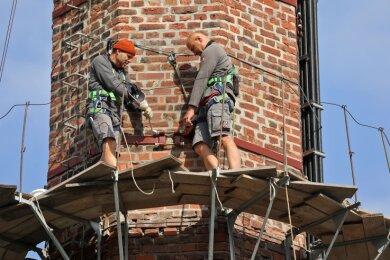 Die Arbeit auf dem schmalen Konsolgerüst ist nicht ungefährlich. Mit Sicherheitsgurten schützen sich die Männer gegen Absturz.