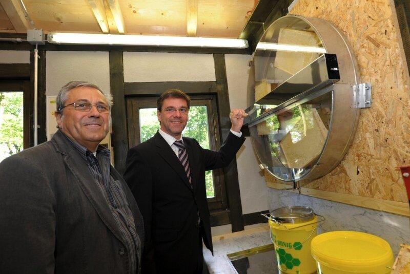 Landwirtschaftsminister Frank Kupfer (r.) lässt sich von Imkerlandesverbandschef Roland Wicht im Bienenhaus auf der Landesgartenschau die Funktionsweise der Wandhonigschleuder erklären.