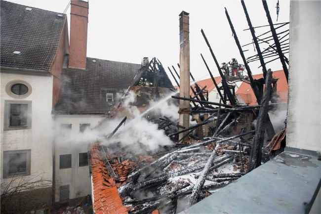 Rauchschwaden wabern durch die Luft: Feuerwehrmänner löschen im Dachstuhl, vom dem nur ein Gerippe übrig blieb, Glutnester.