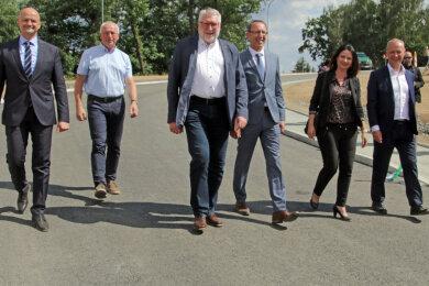 André Wendt (MdL, AfD), Halsbrückes Bürgermeister Andreas Beger (CDU), Landrat Matthias Damm (CDU), Jörg Urban (MdL, AfD), Susan Leithoff (MdL; CDU) und Jens Albrecht, Abteilungsleiter Mobilität im SMWA (v.l.), schreiten die neue Straße ab.