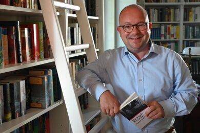 Frank Müller-Rosentritt am heimischen Bücherregal.