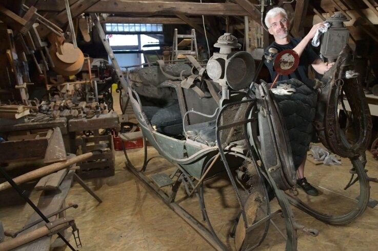 Die Friedrich-August-Schmiede in Großschirma. Tim Meyer in seinem Refugium unterm Dach mit einem historischen Pferdeschlitten und Werkzeugen verschiedener Handwerkszünfte.