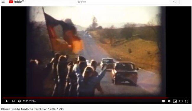 Winkende Menschen mit einer Fahne, deren DDR-Emblem herausgeschnitten ist.