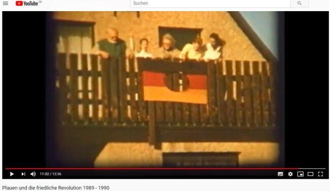 Auf dem Balkon zeigt eine Familie eine Fahne ohne DDR-Emblem.