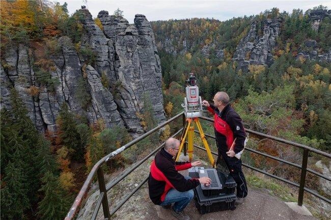 Ausgerichtet: Die Techniker Thomas Martienßen (links) und Michael Ufer bauen ihren Laserscanner am ersten Messpunkt inmitten der Felsenburg Neurathen auf, direkt gegenüber den Wehltürmen.