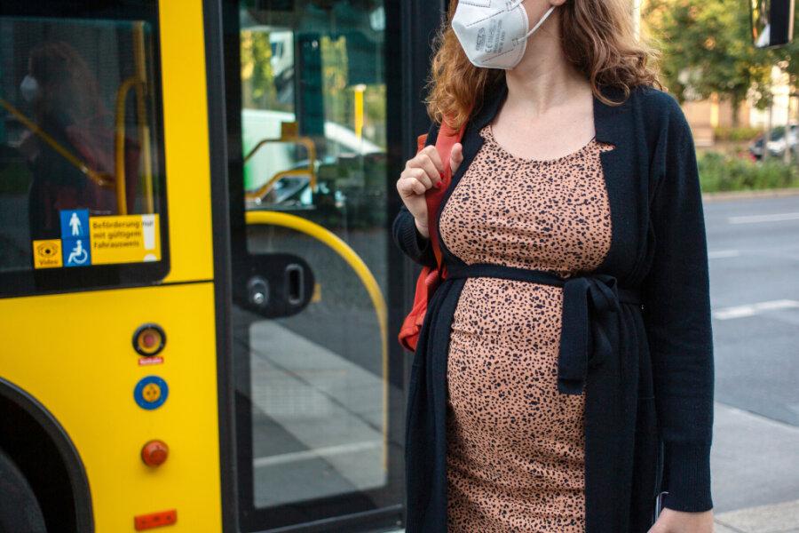 ine schwangere Frau wartet mit Mund-Nasen-Schutz an einer Haltestelle auf dem Bus. Die Ständige Impfkommission (Stiko) will sich am Freitagvormittag erneut zur Impfung von Schwangeren äußern.