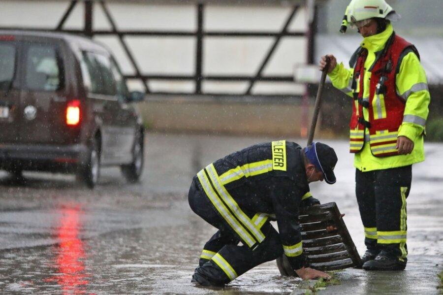 Feuerwehrleute heben die Gullydeckel aus der Fahrbahn. Die Siebe der Einläufe waren mit Schlamm und Dreck zugesetzt, sodass die Gullys die Wassermassen nicht mehr schlucken konnten.