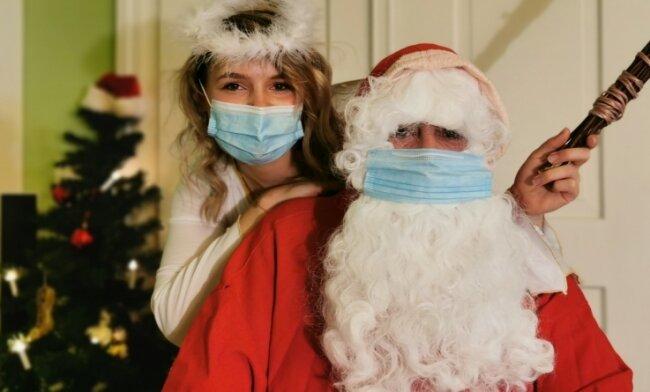 Jennifer Martens und Lars Herrmann als Engel und Weihnachtsmann. Für die Fotogrüße an die Kinder kommt die Maske ab.