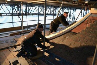 Dachdecker im Dienst der Dombauhütte: Das Dach der Taufkapelle des Aachener Doms wird neu verschiefert.