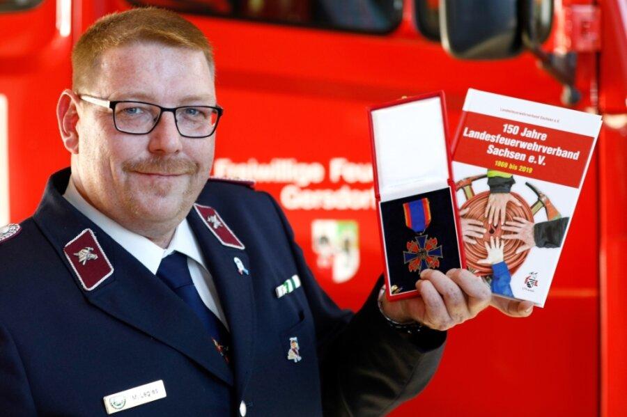 Mario Legies mit seinem Feuerwehr-Ehrenkreuz und der Chronik, die er zusammen mit anderen Feuerwehrleuten verfasst hat.