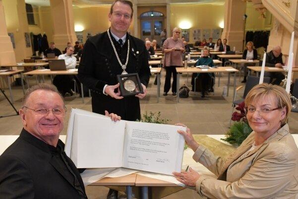 Rommi und Roland Säurich wurden für ihre Verdienste um den Erhalt des Tivoli von OB Sven Krüger (m.) mit der Ehrenmedaille der Stadt ausgezeichnet. Zudem trugen sie sich in das Goldene Buch der Stadt Freiberg ein.
