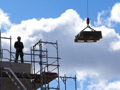 Ein Arbeiter dirigiert auf einer Baustelle einen Kran.