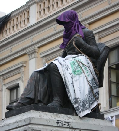 Die Statue des Gründers der Universidad de Chile, Andrés Bello, von Protestierenden in eine Dollarnote eingehüllt.