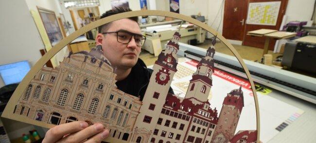Robert Kahmann prüft die Motivplatte eines Schwibbogens, der die Chemnitzer Innenstadt zeigt. Die Bauteile werden bei der Niederfrohnaer Firma Holz-nischel maschinell hergestellt und dann in Handarbeit zusammengebaut.